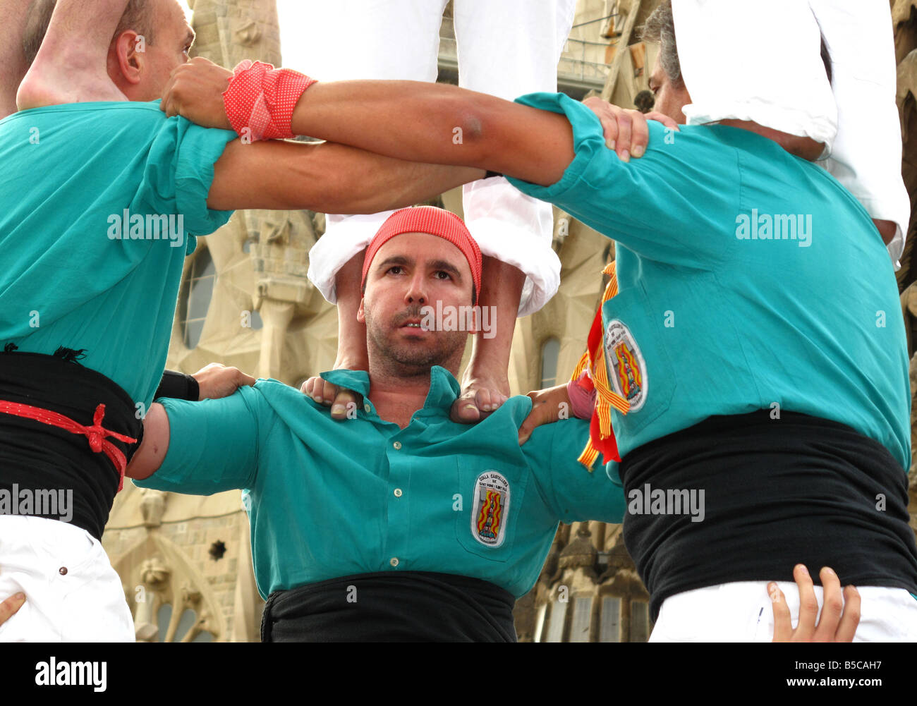 Close-up of Castellers human tower(castell)buildering outside Gaudi's La Sagrada Familia Cathedral, Barcelon, - Stock Image