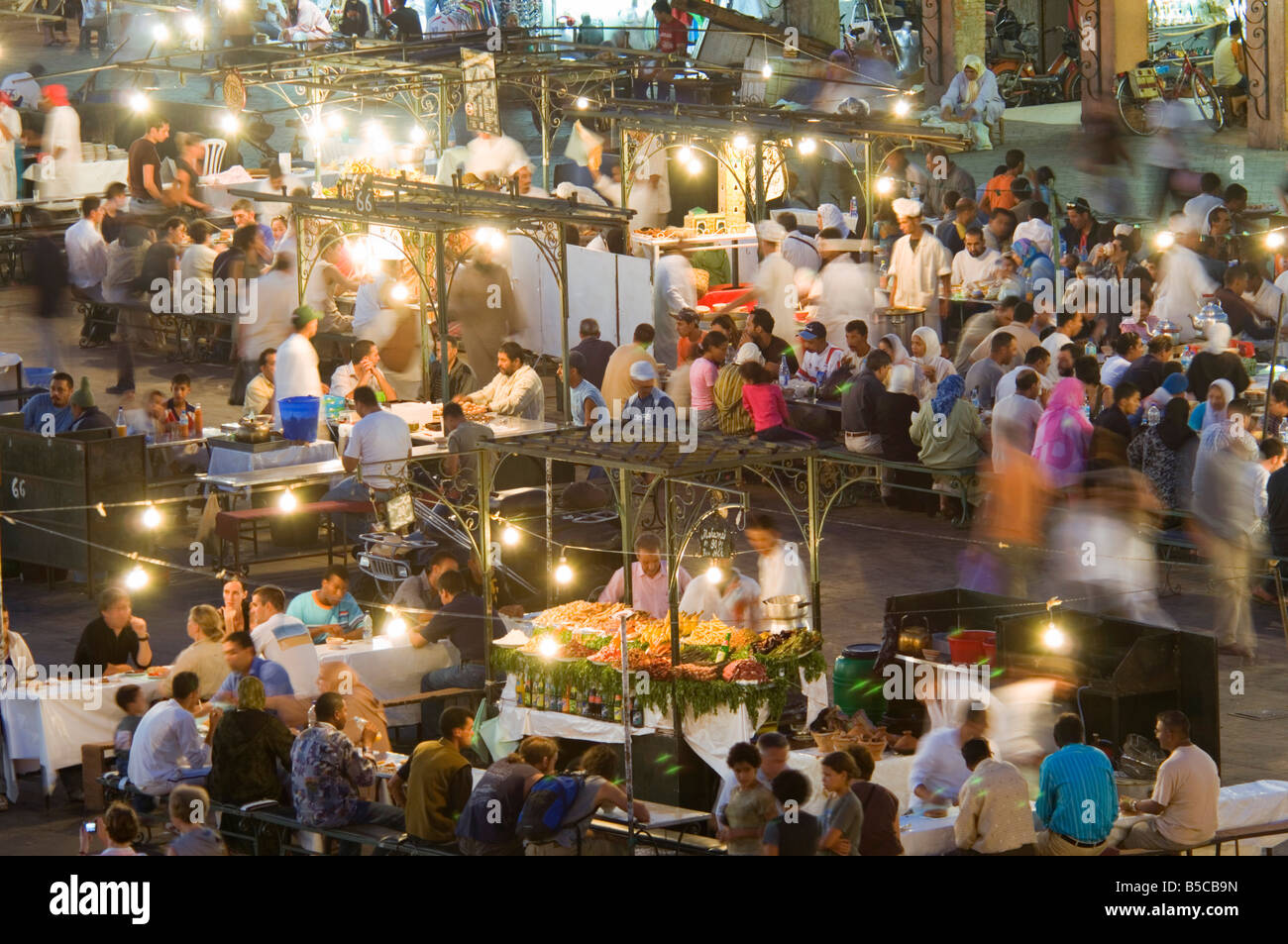 A compressed perspective aerial view of the open air 'restaurants' at the Djemaa El Fna with slow shutter - Stock Image