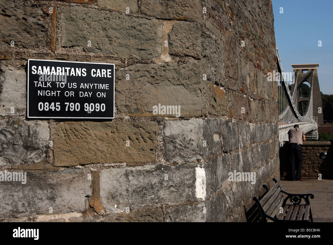 Samaritans sign and suicide helpline on [Clifton Suspension Bridge], lonely man in background, Bristol, England, Stock Photo