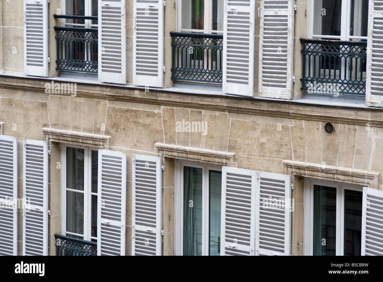 Façade windows shutters Juliet balcony metal stone building apartment condo repetition louvered paris france glass Stock Photo
