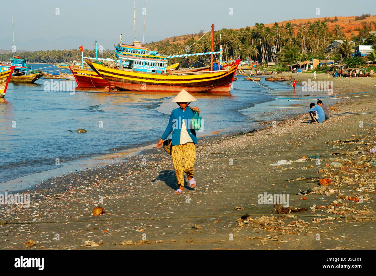 Fisher woman walks along the fishermen's beach of Mui Ne, Viet Nam - Stock Image