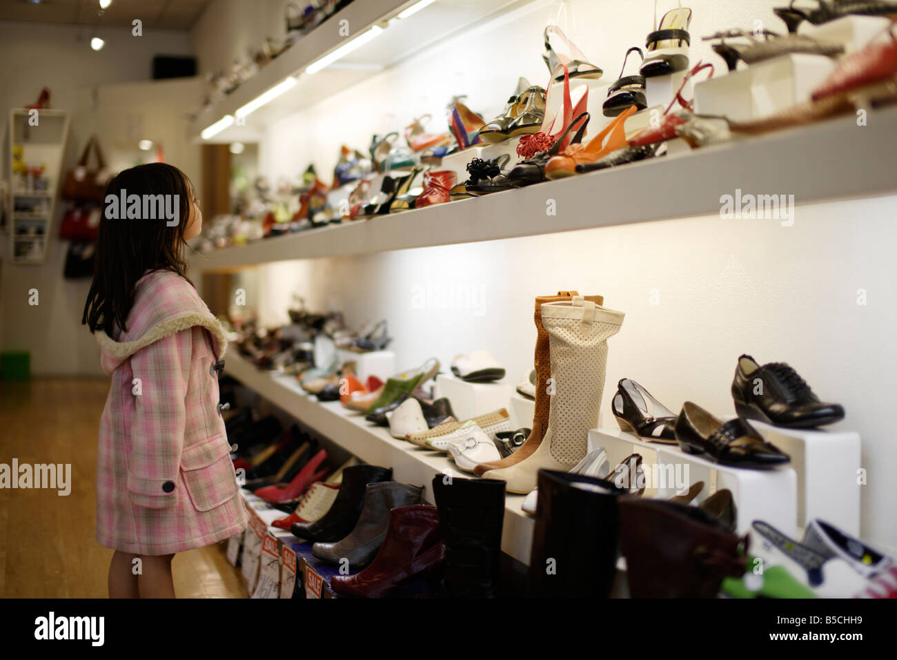 Girl six years old admires shoes in shop Stock Photo