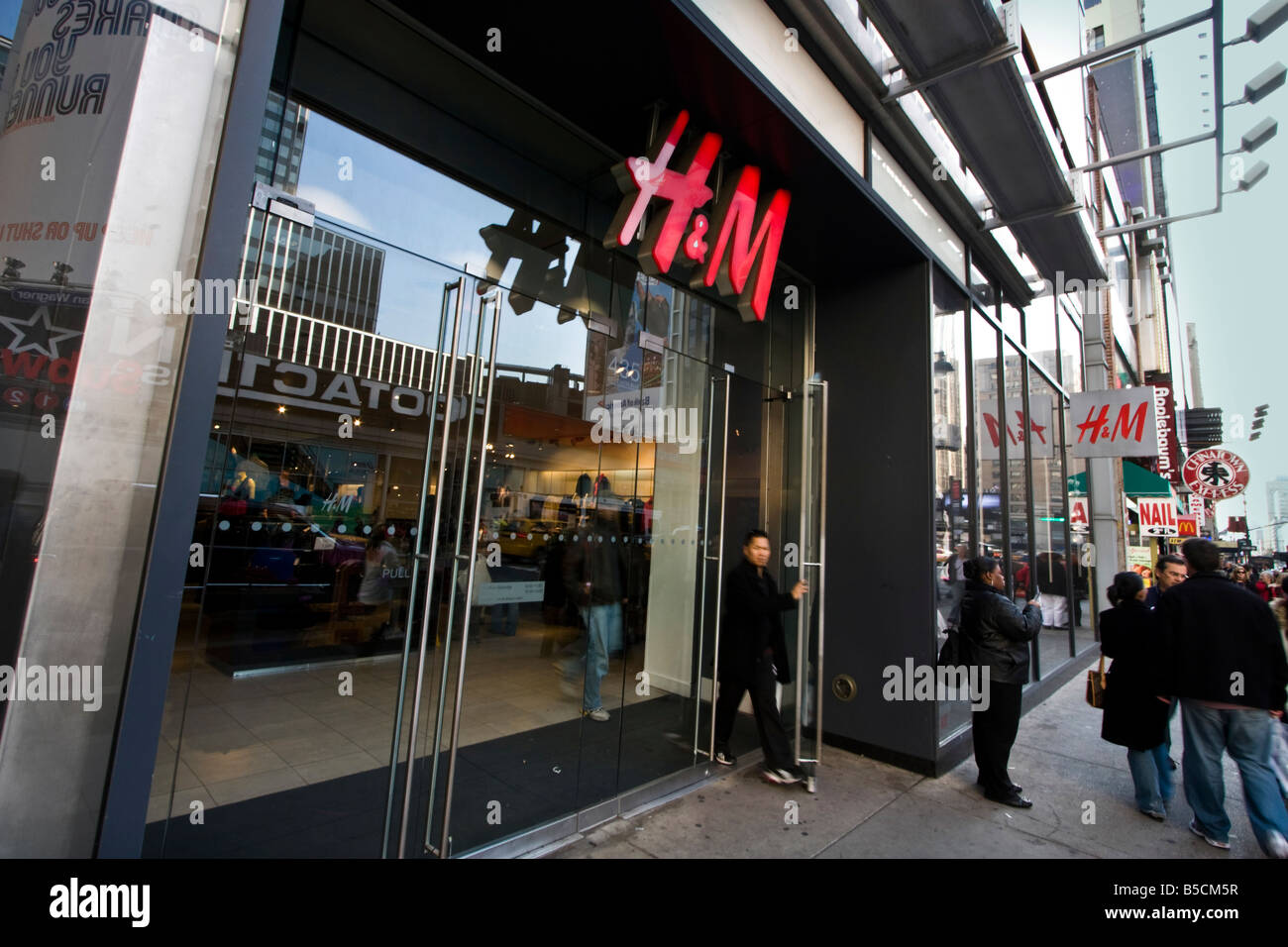 A shopper is seen exiting a branch of H&M in New York. Stock Photo