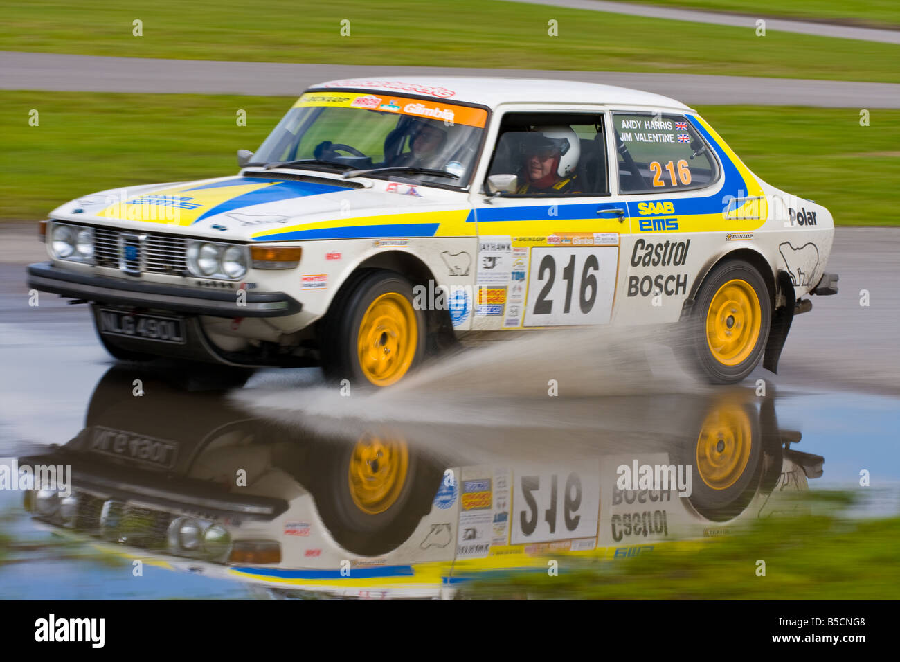 A classic Saab 99 going through a water splash with a great reflection - Stock Image