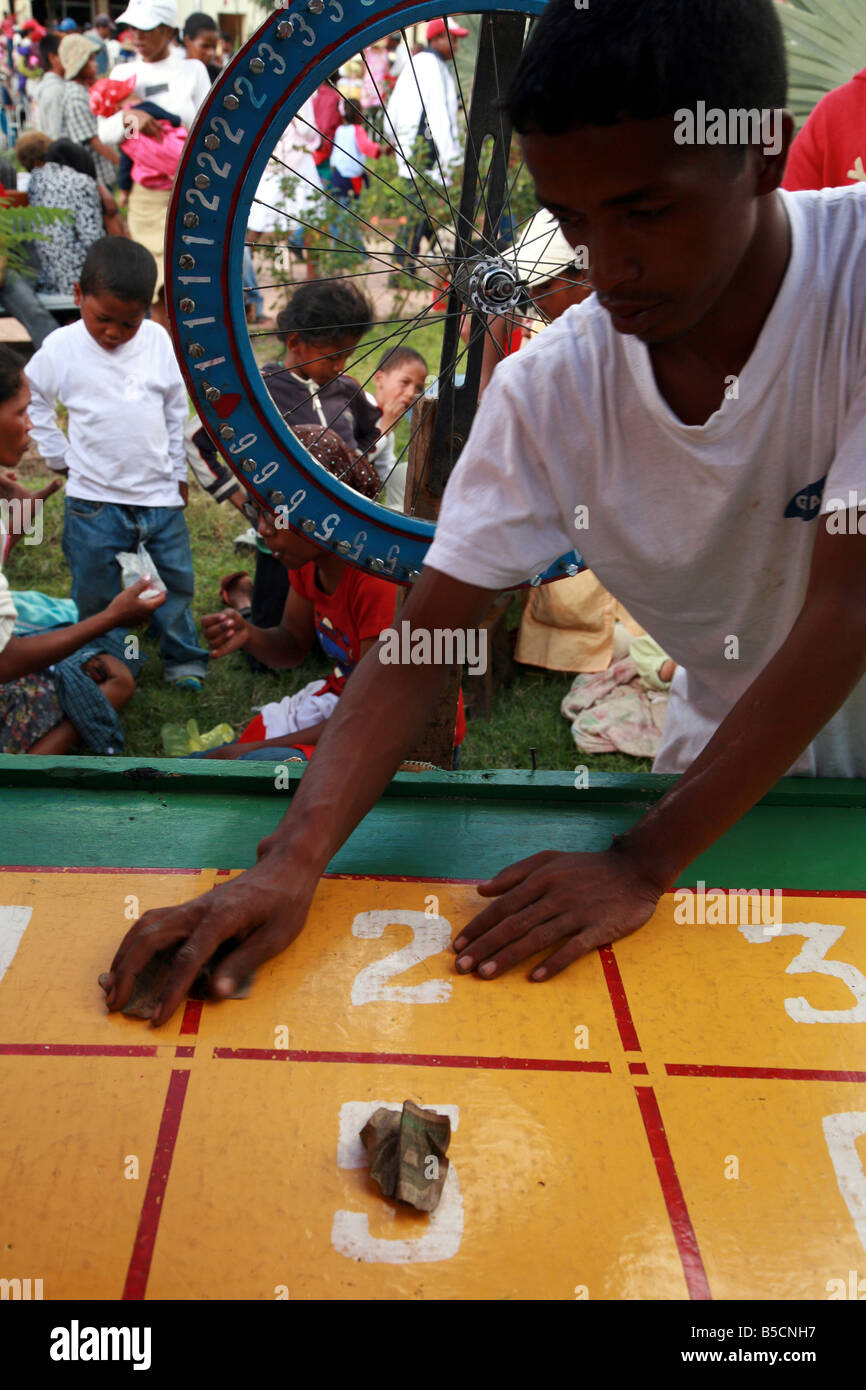 A man giving back money to a winner to lotto at the traditional May fair of Antanarivo Madagascar - Stock Image