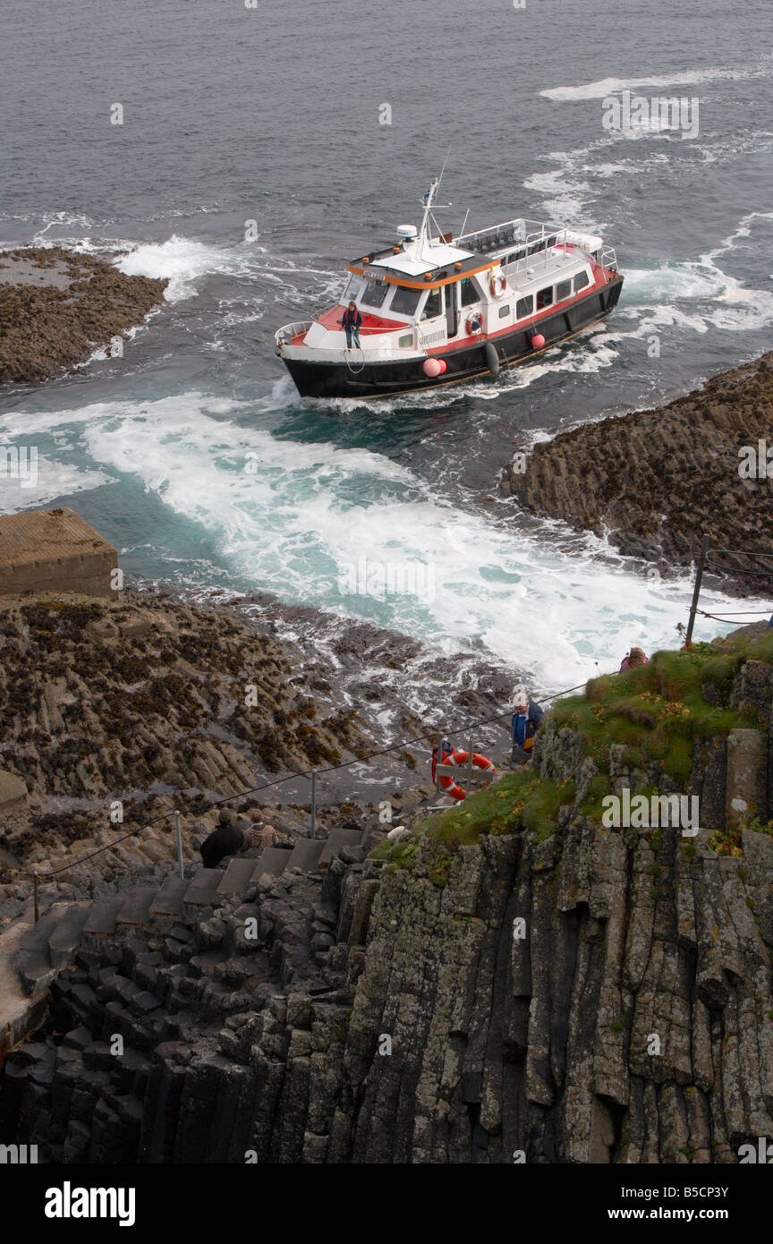 tourist pleasure boat coming in to land at the stone jetty on the island of staffa in argyll in scotland - Stock Image