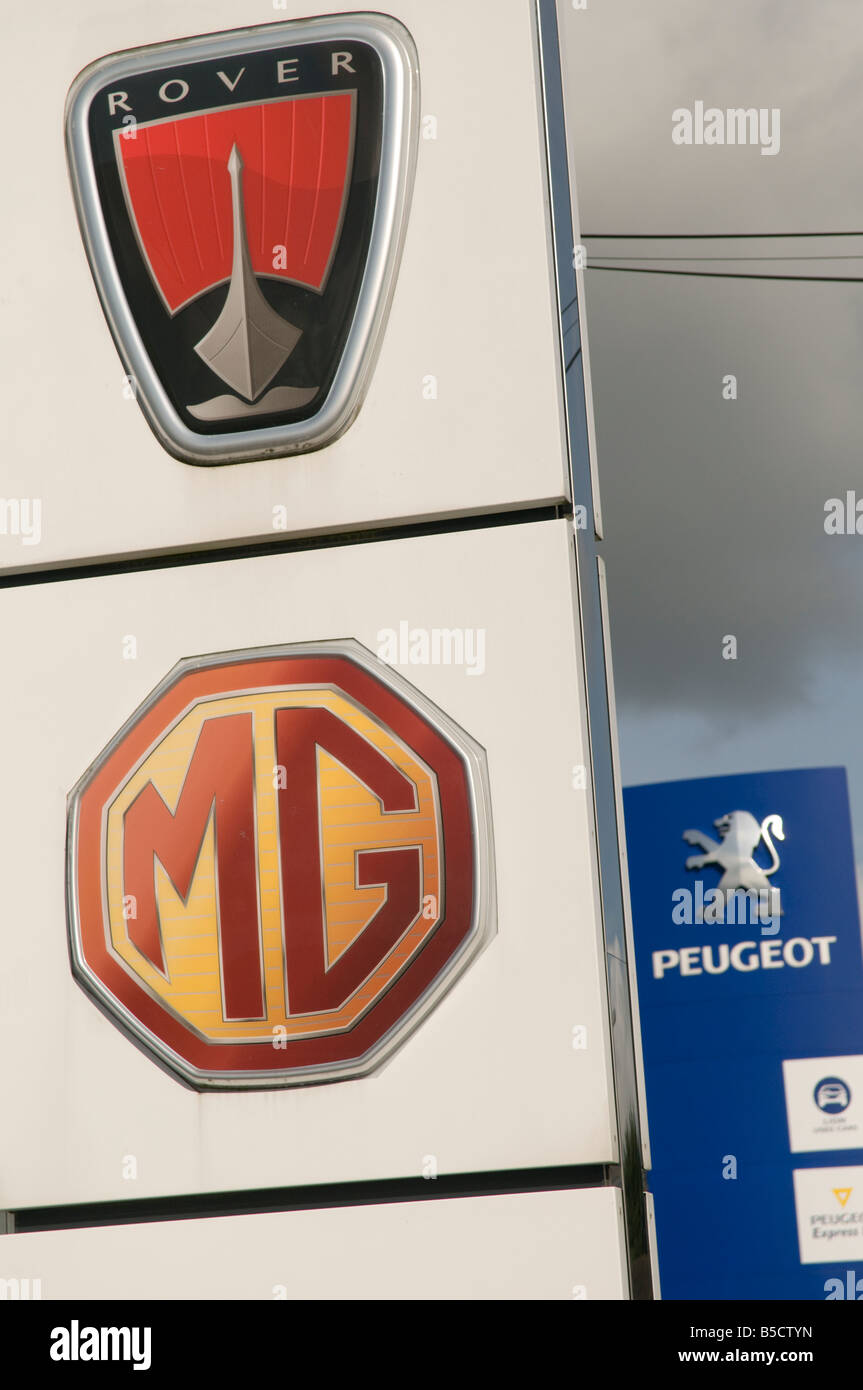 Rover Peugeot and MG car makers symbols on garage forecourt - Stock Image