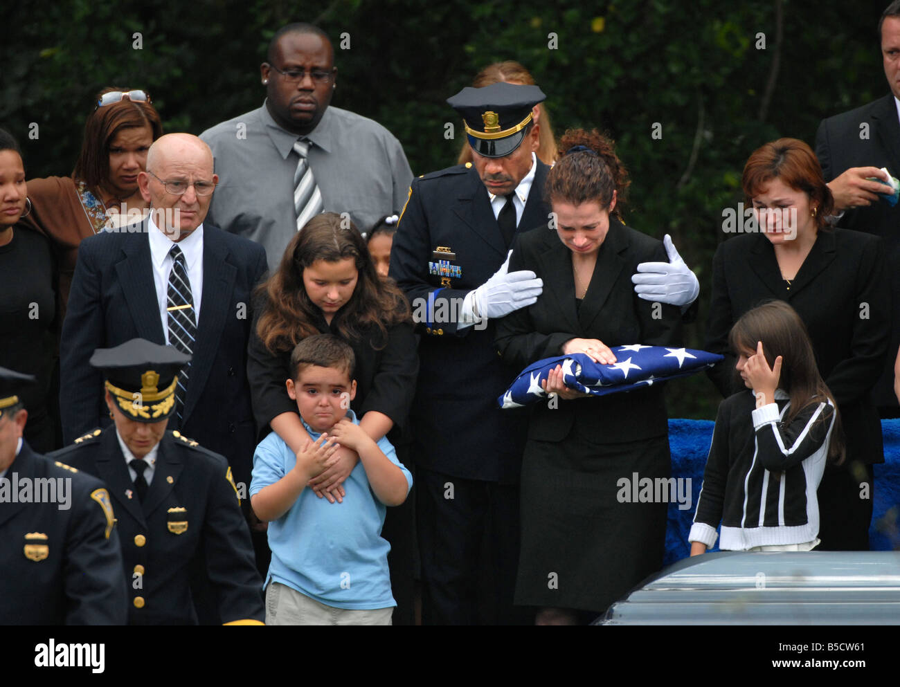 a police funeral with the family mourning after receiving the flag