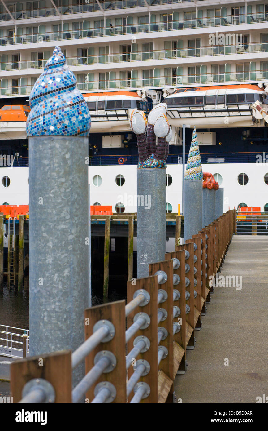Decorative sculptures on top of floating pier supports decorated with brightly colored tiles in Ketchikan Alaska - Stock Image