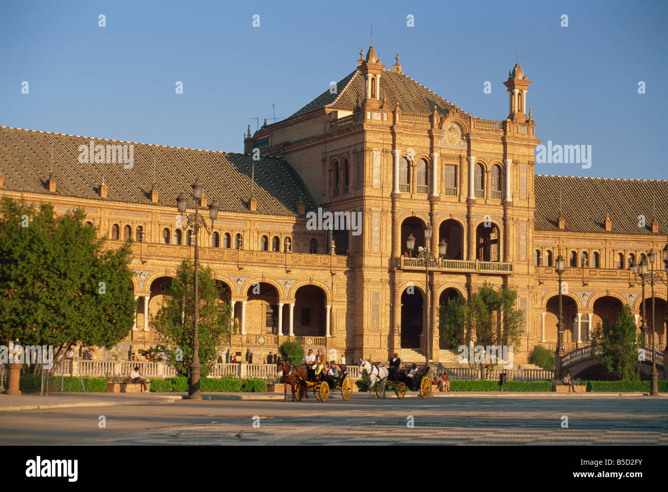 Horse-drawn carraiges and the Palacio Espanol at sunset, Plaza de Espana, Parque de Maria Luisa, Seville, Andalucia, - Stock Image