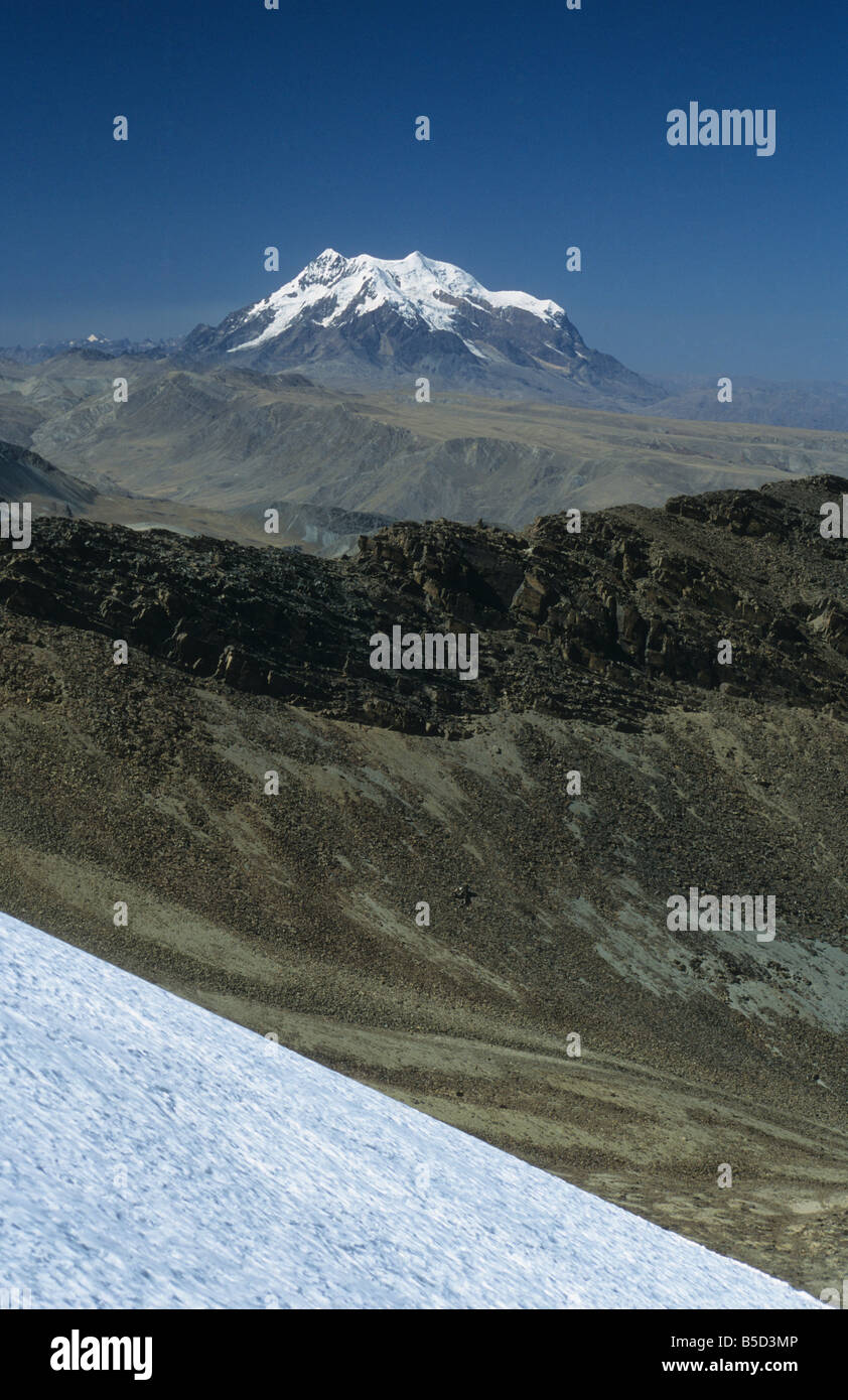 Mt Illimani seen from Mt. Chacaltaya glacier, scree slopes below ridge in middle distance, Cordillera Real, Bolivia Stock Photo