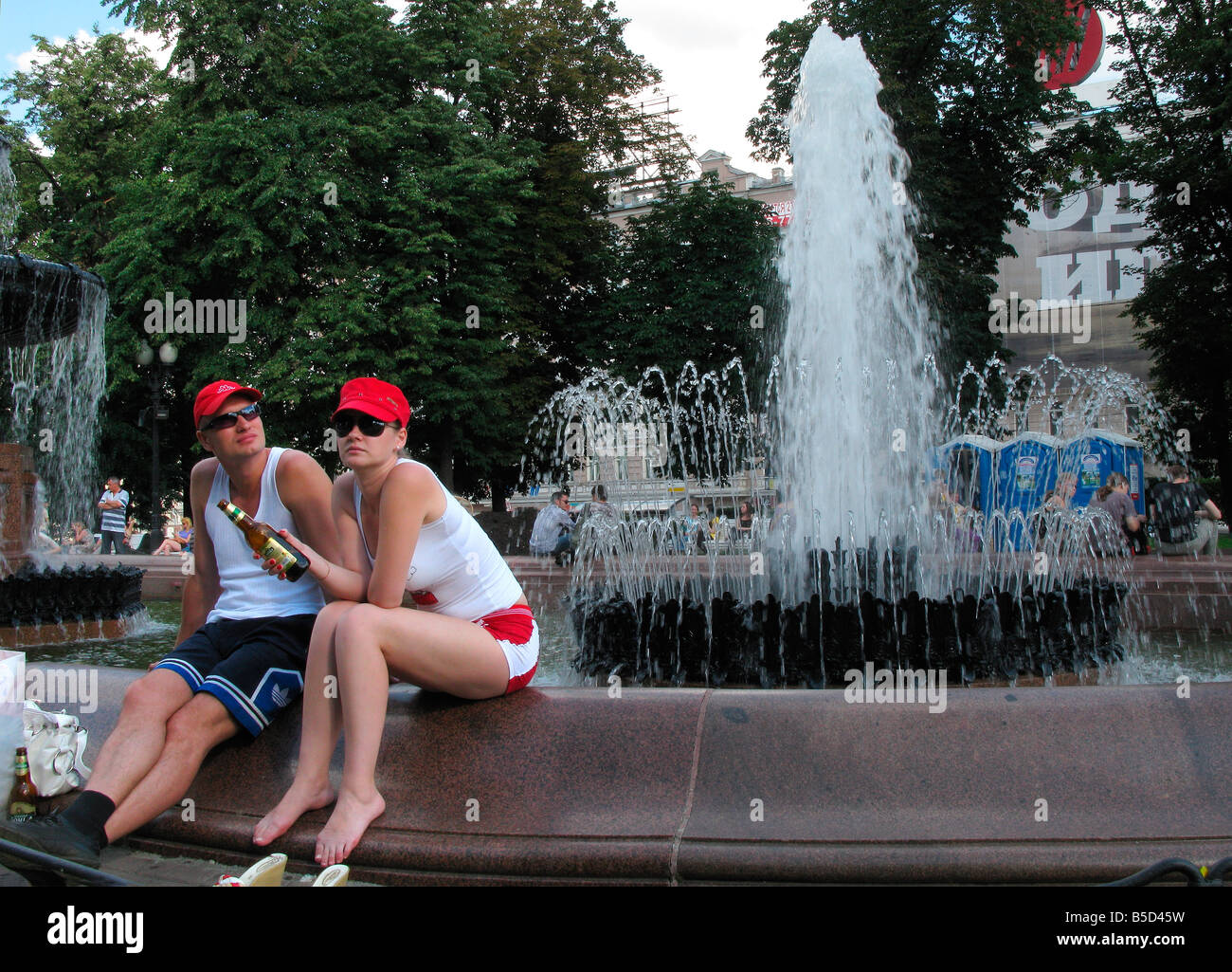Two young people with red hats siting near fontain in the centre of Moscow (Pushkin squire),  in hot summer day, - Stock Image