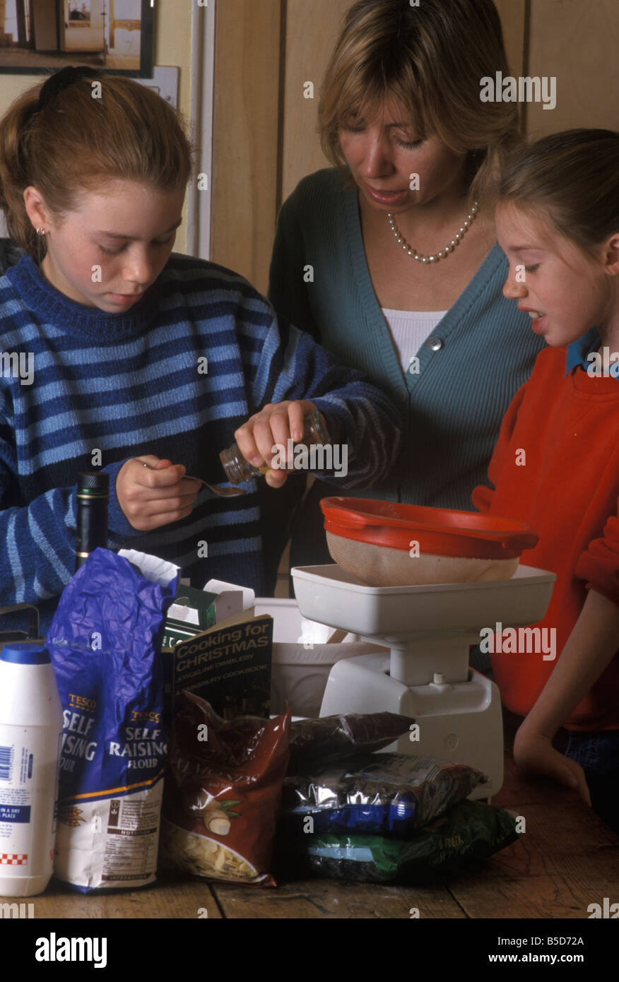 mother and daughters cooking a Christmas cake - Stock Image