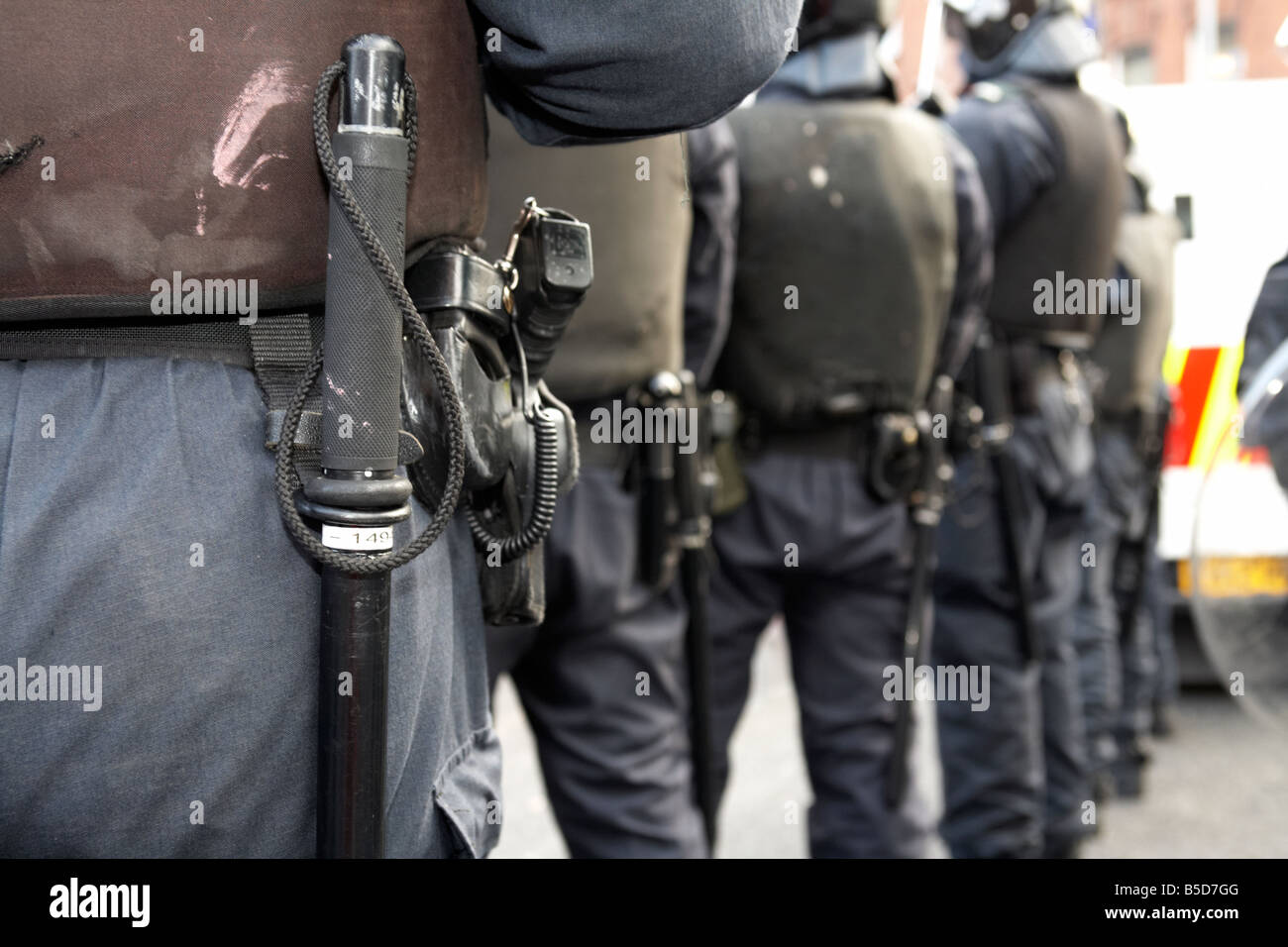 row of PSNI Police Service of Northern Ireland riot squad officers wearing batons sidearms and riot gear - Stock Image