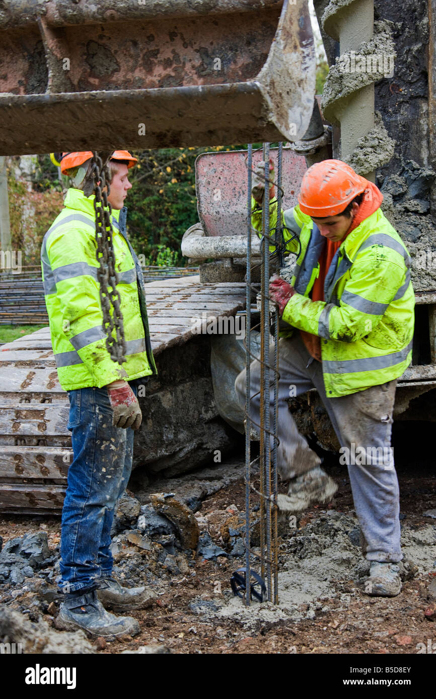 Workmen working the steel reinforcement bars down into concrete piles. - Stock Image