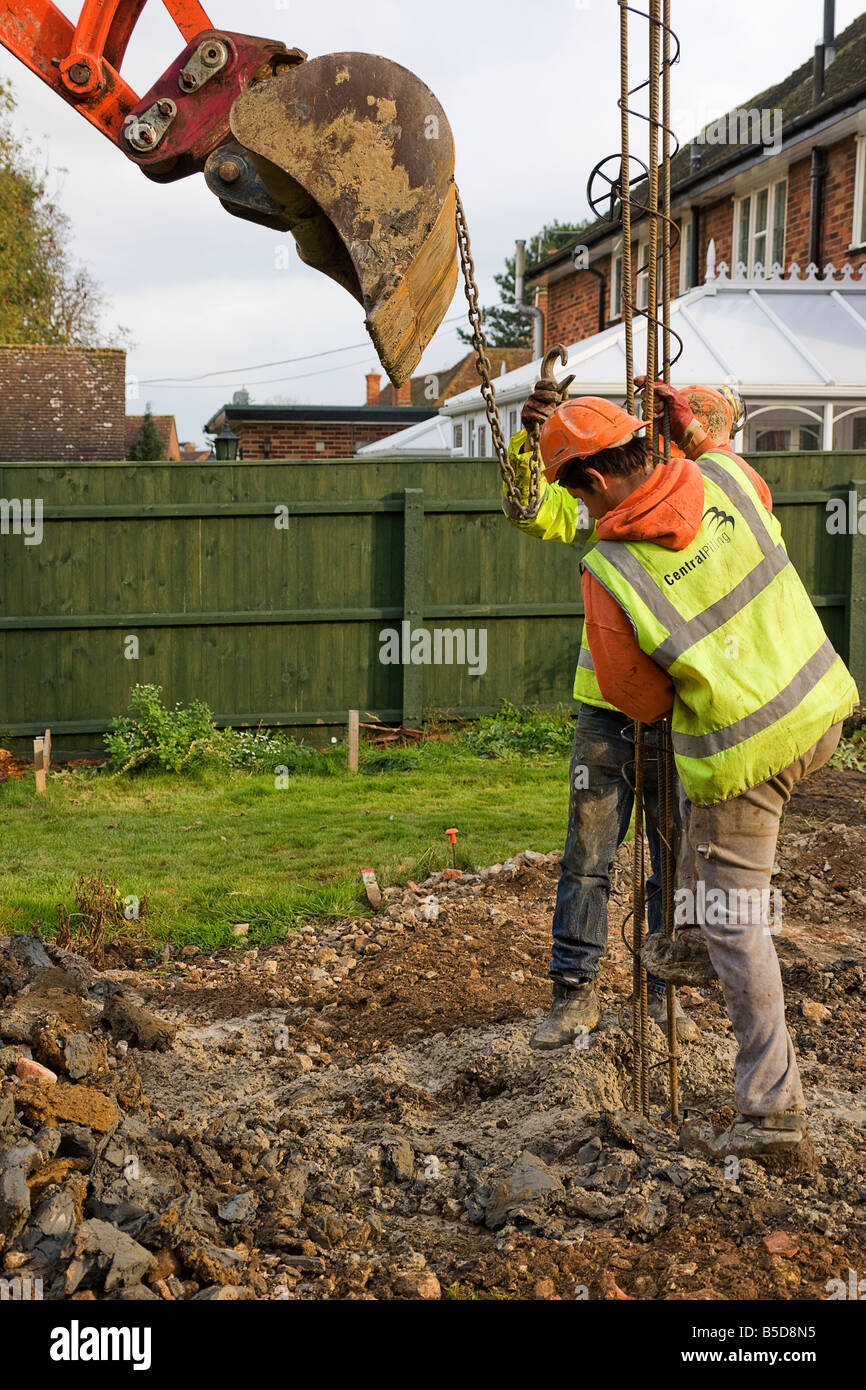 Workmen inserting steel reinforcement bars into concrete piles. - Stock Image