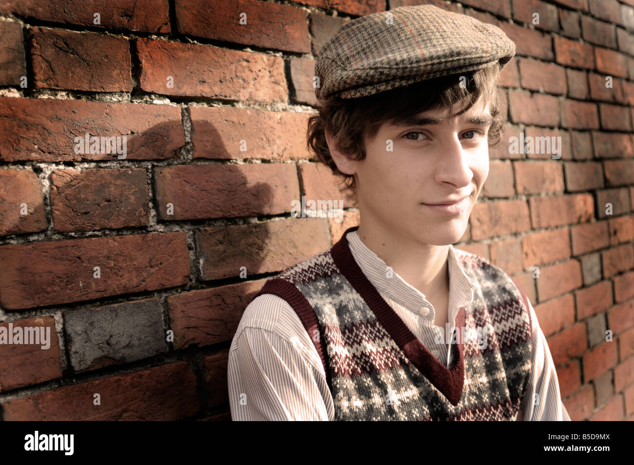 Royalty free photograph of British boy evacuee in wartime standing by brick wall looking lonely with 1940s style - Stock Image