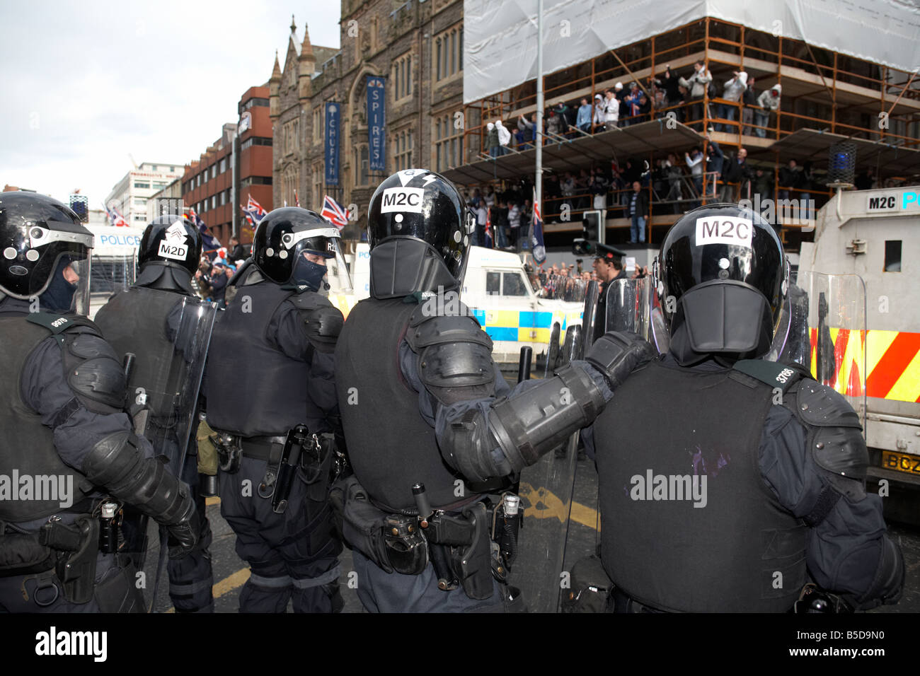 line of PSNI Police Service of Northern Ireland riot squad control officers form defensive line during loyalist - Stock Image