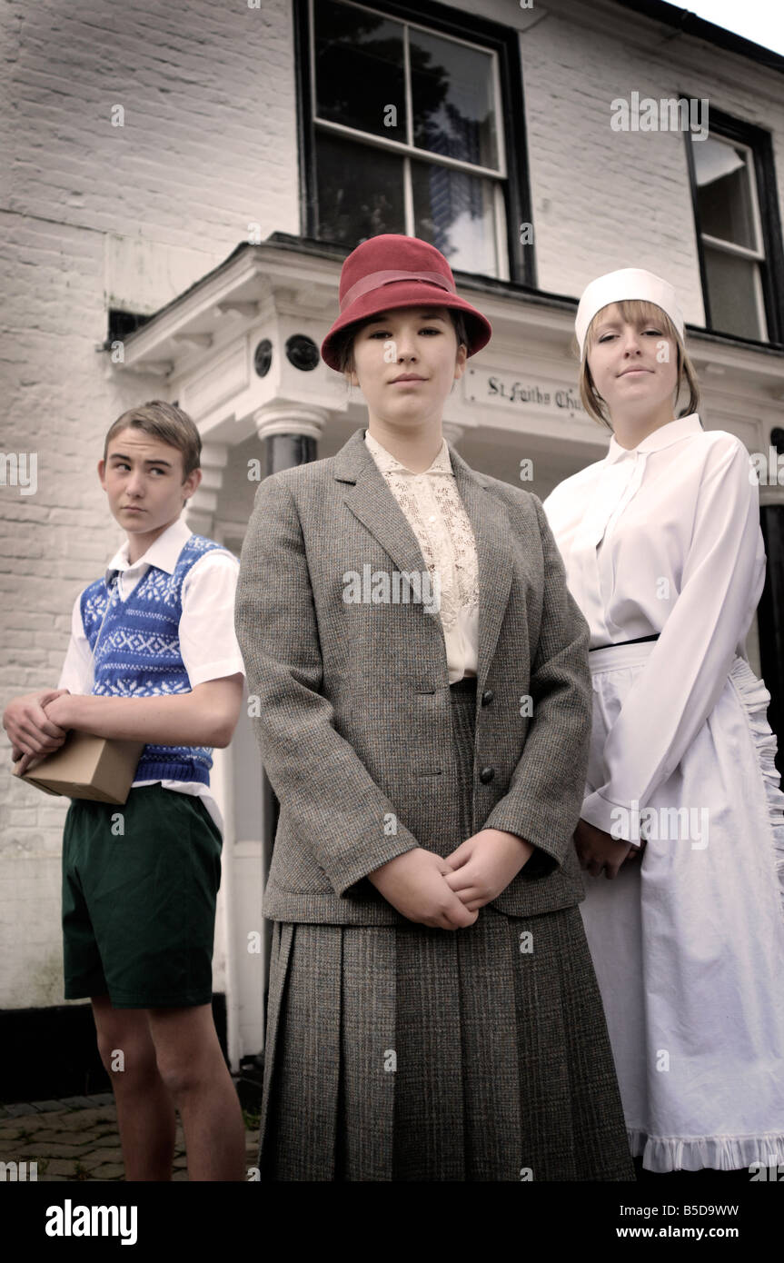 Royalty free photograph of British lady with girl housekeeper and boy evacuee outside the family house. - Stock Image
