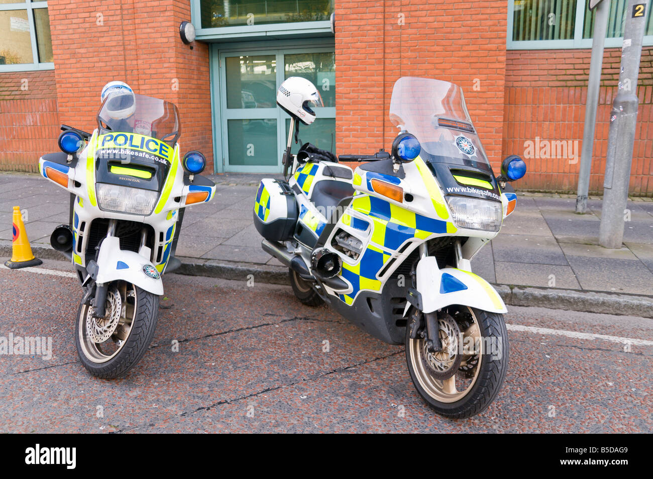 Police Service of Northern Ireland (PSNI) motorcycles parked at a roadside with helmets on rear - Stock Image