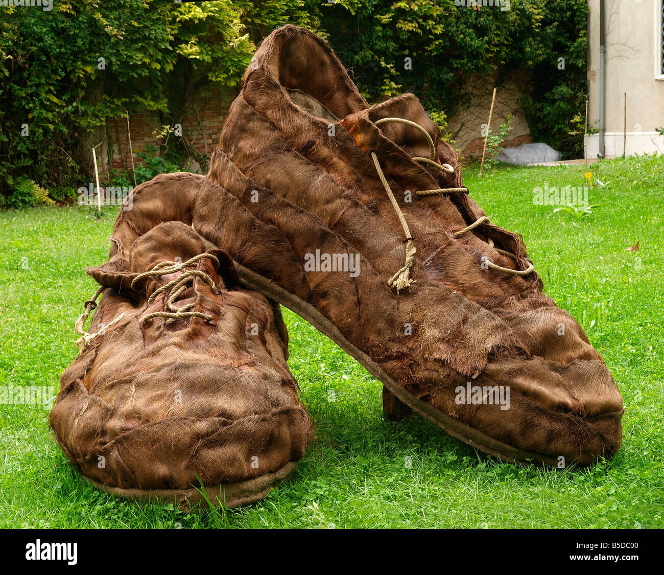 Big Statue of old worn out boots (shoes) in the Park of Portogruaro - Italian city, Northern Italy near Adriatic - Stock Image
