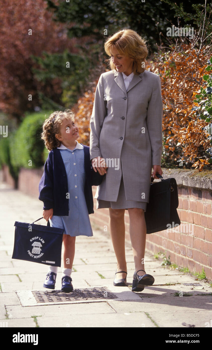 working mother walking her daughter to school at the start of a new term - Stock Image