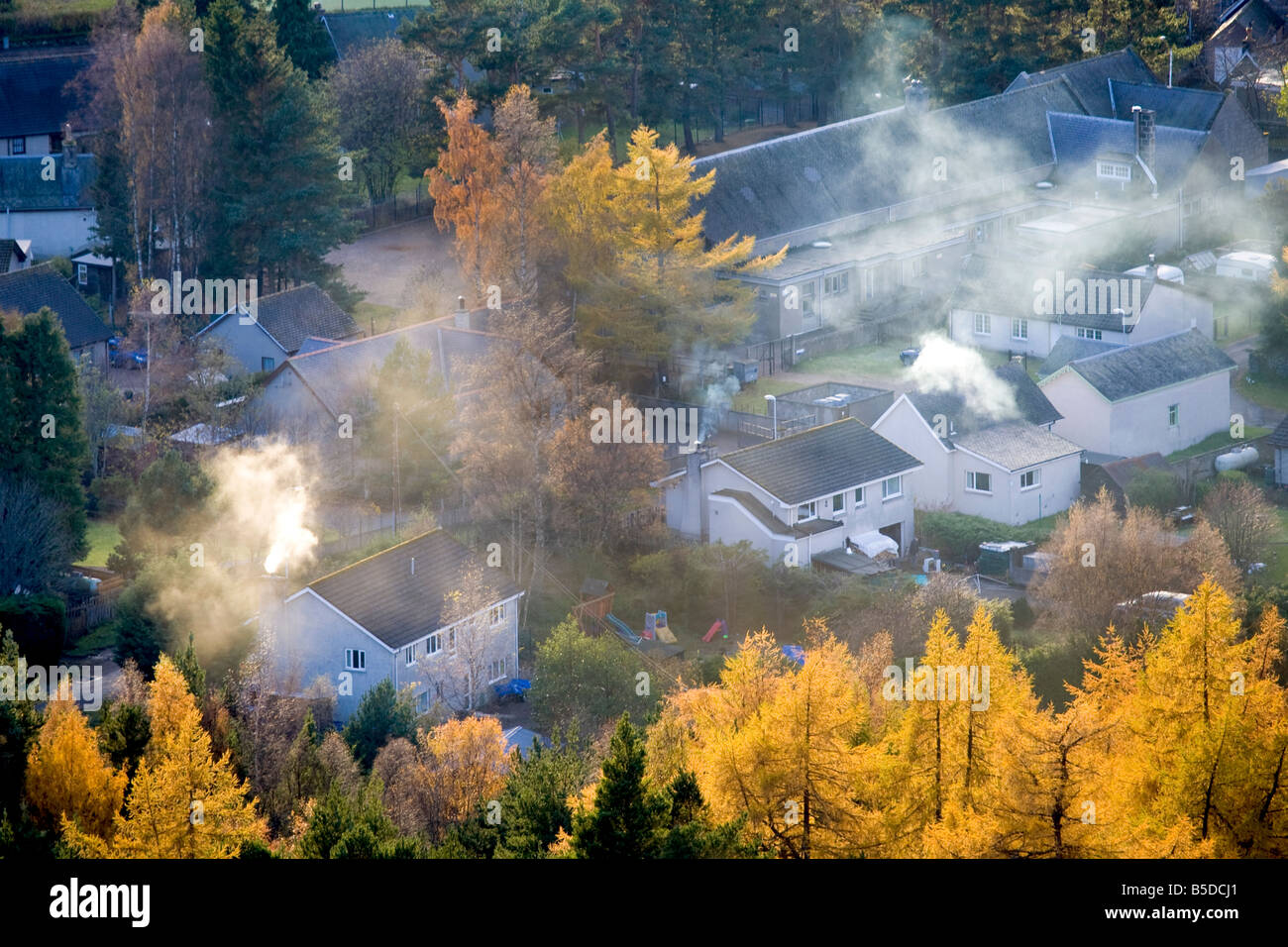 Smoking Chimneys, roofs, with Larch trees in Autumn Foliage.  The Scottish village of Braemar, Aberdeenshire, Cairngorms - Stock Image