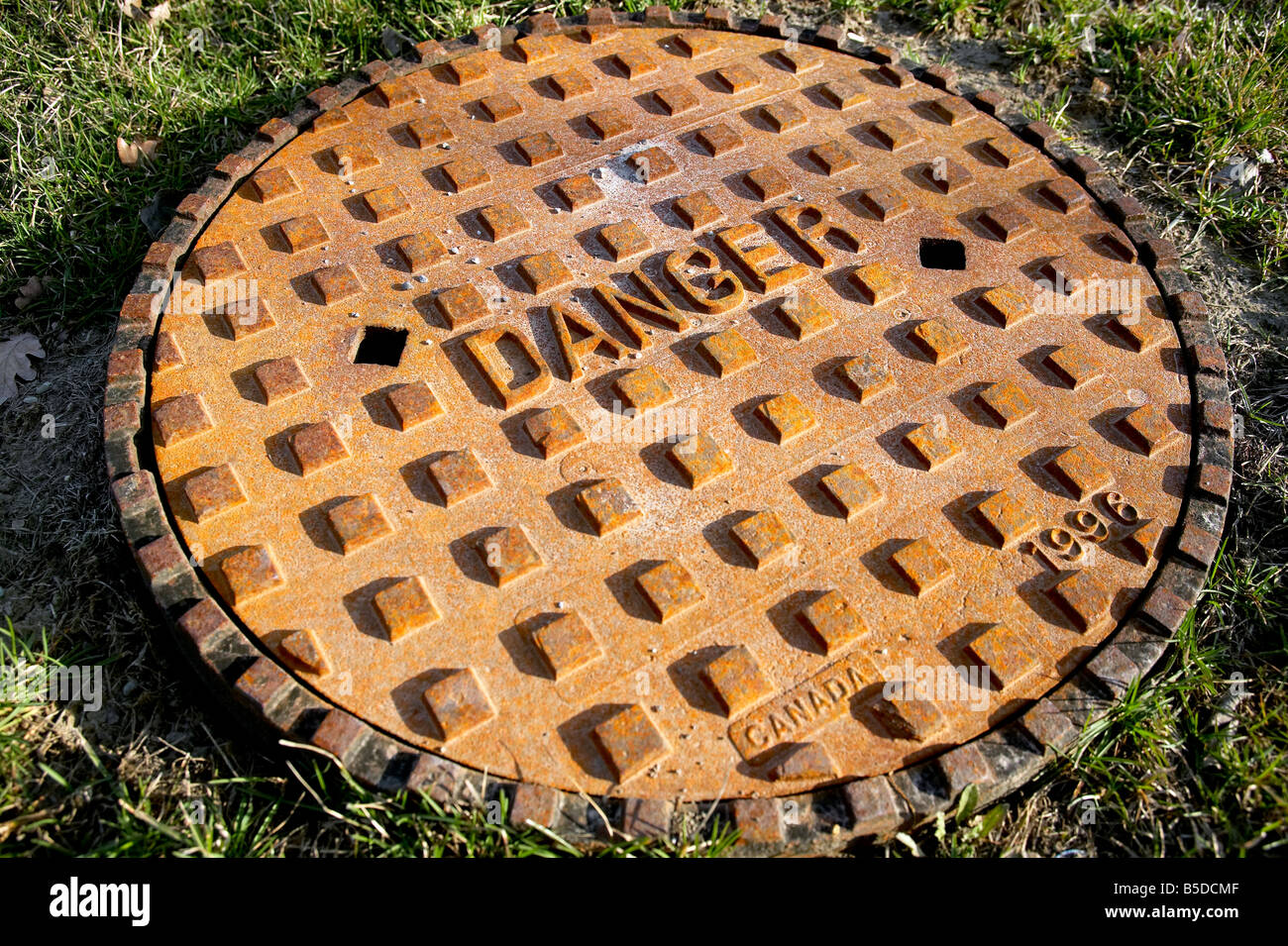 rusted manhole sewer cover reading the word Danger - Stock Image
