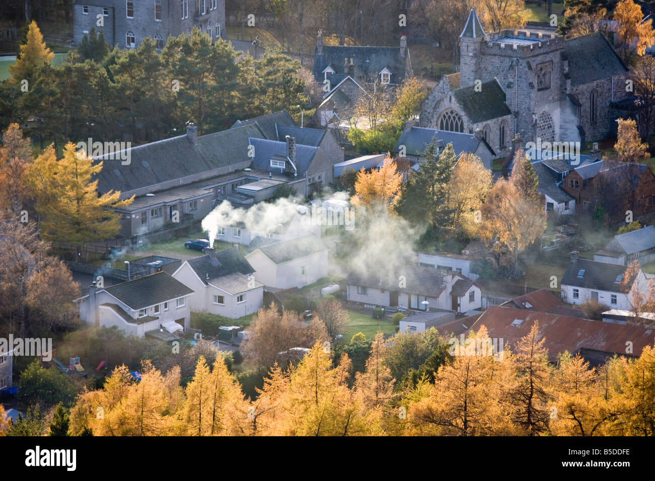 Smoking Chimneys, and roofs, with Larch trees in Autumn season Foliage, in the Scottish village to Braemar, Cairngorms - Stock Image