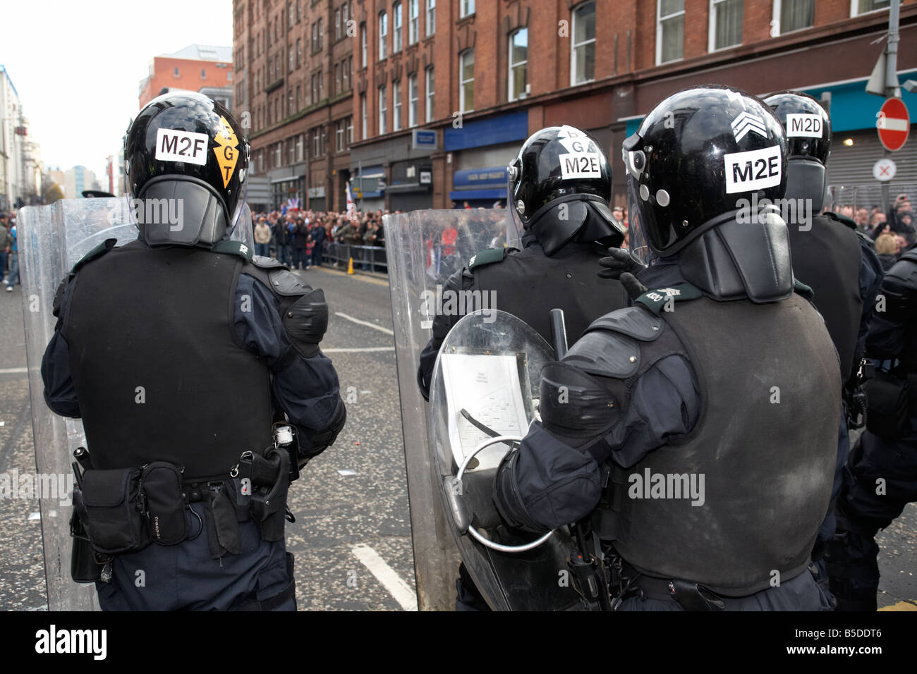 PSNI Police Service of Northern Ireland riot control officers standing guarding during loyalist protest parade belfast - Stock Image