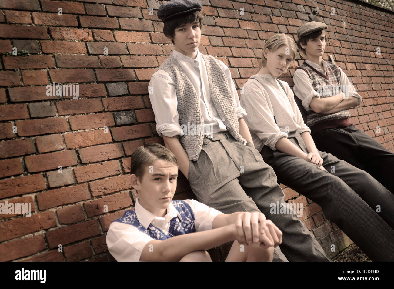 Royalty free photograph of British boys evacuees in wartime standing by brick wall looking lonely with 1940s style - Stock Image