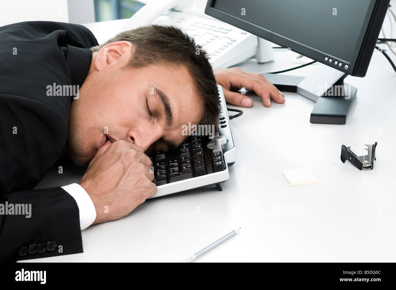 Businessman sleeping at workplace, close up - Stock Image