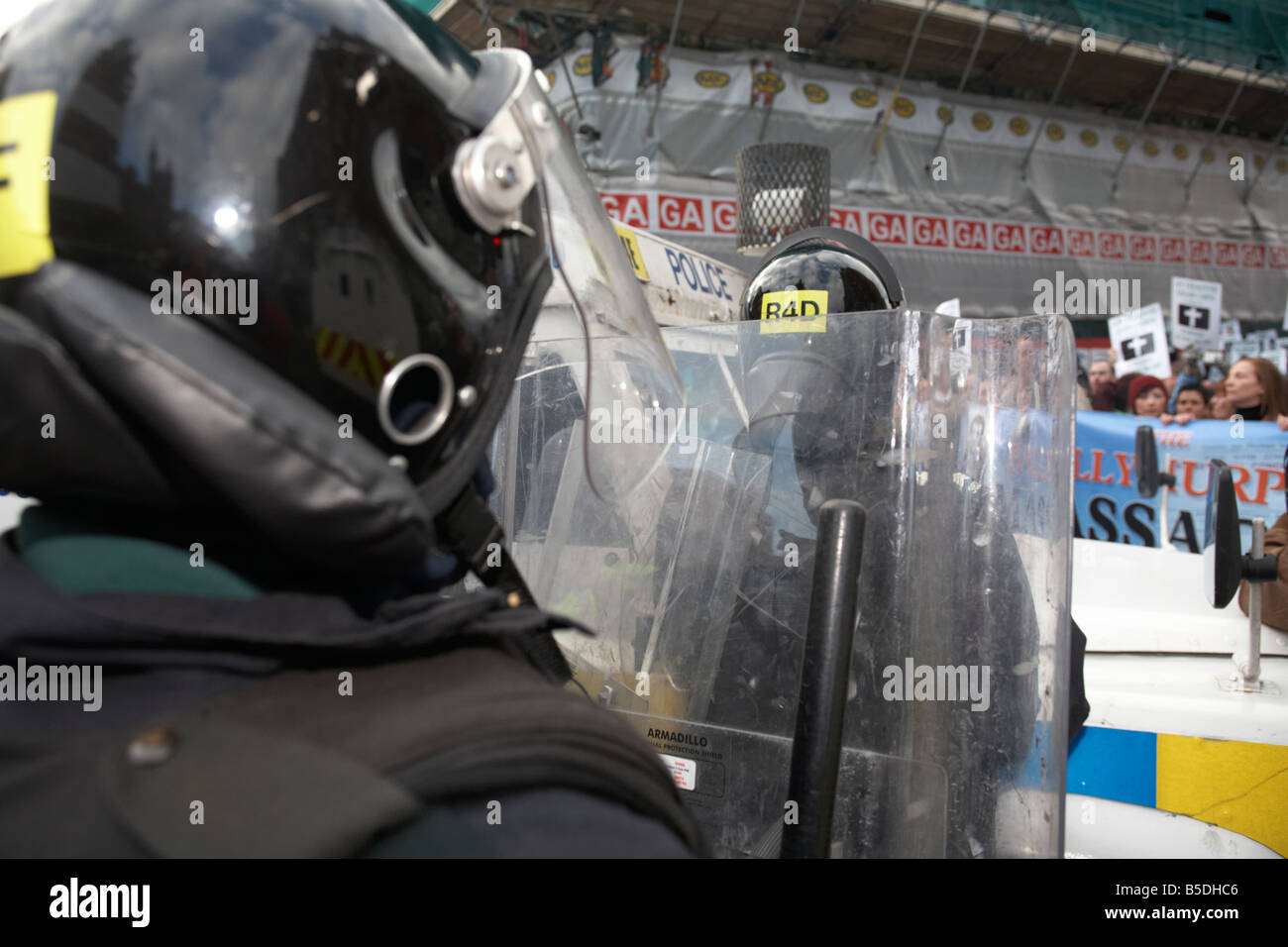 PSNI Police Service of Northern Ireland riot control officer stands guard with helmet and riot shield during republican - Stock Image