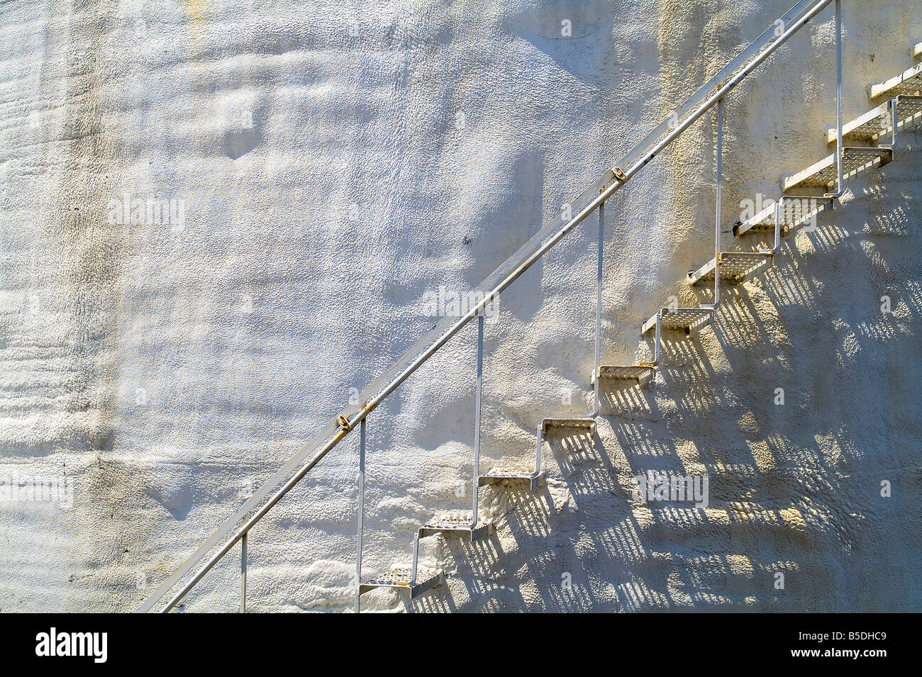 Old Metal Stairs On Side Of White Stucco Storage Tank With Rust Stains, USA - Stock Image