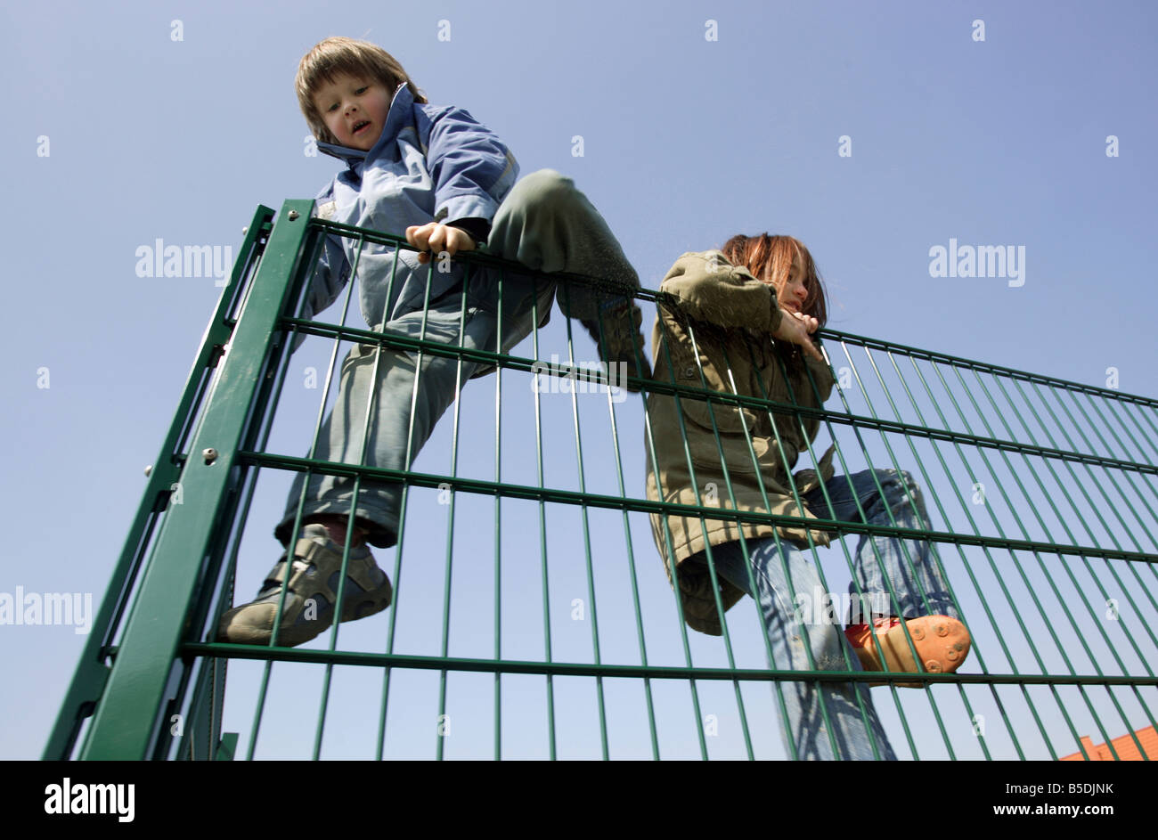A boy and a girl climbing over a fence - Stock Image