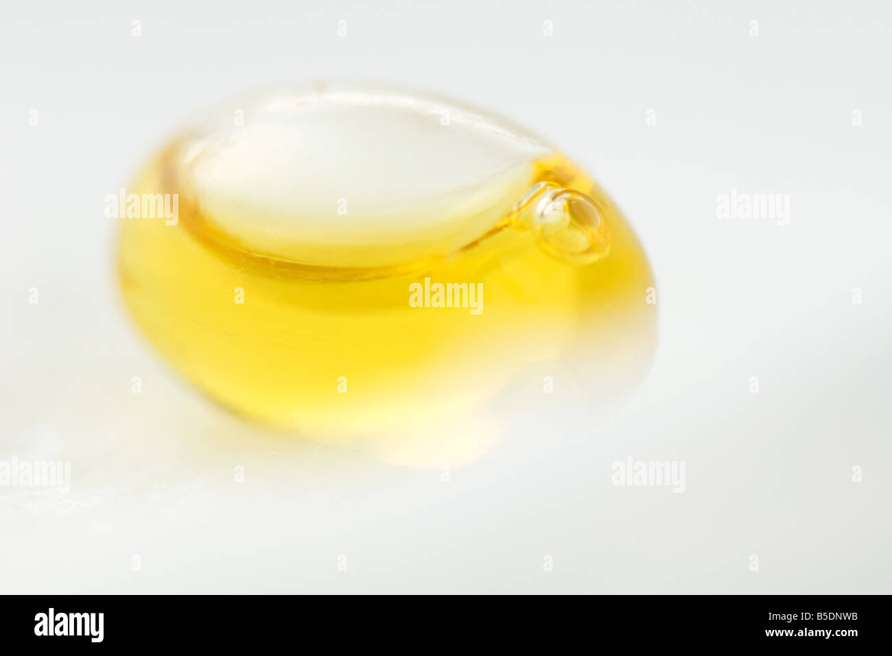 Yellow liquid inside of egg-shaped container, close-up - Stock Image