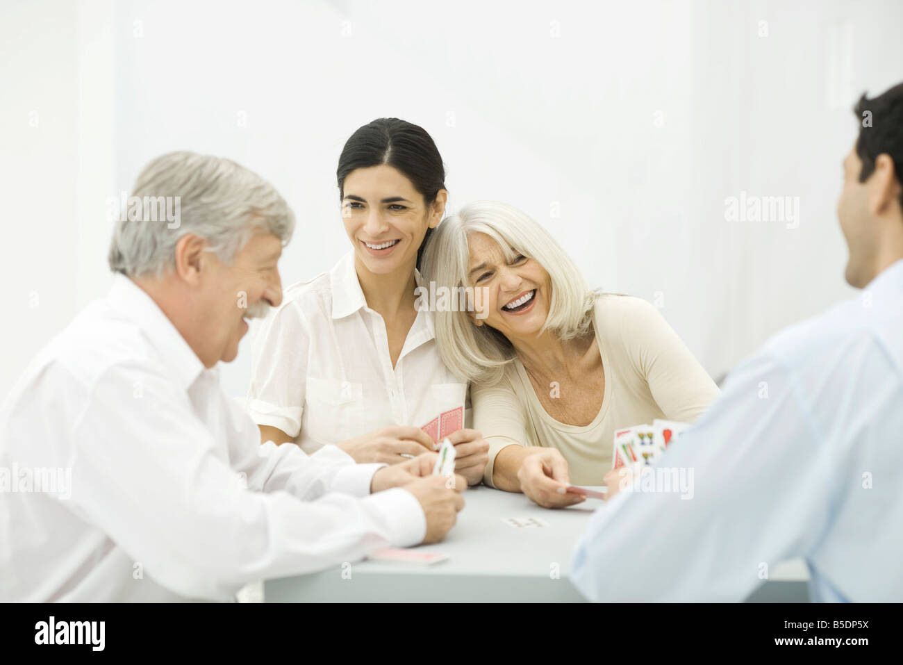Family playing cards, laughing - Stock Image