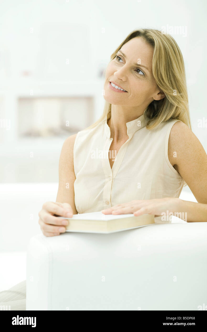 Woman holding closed book, looking away - Stock Image