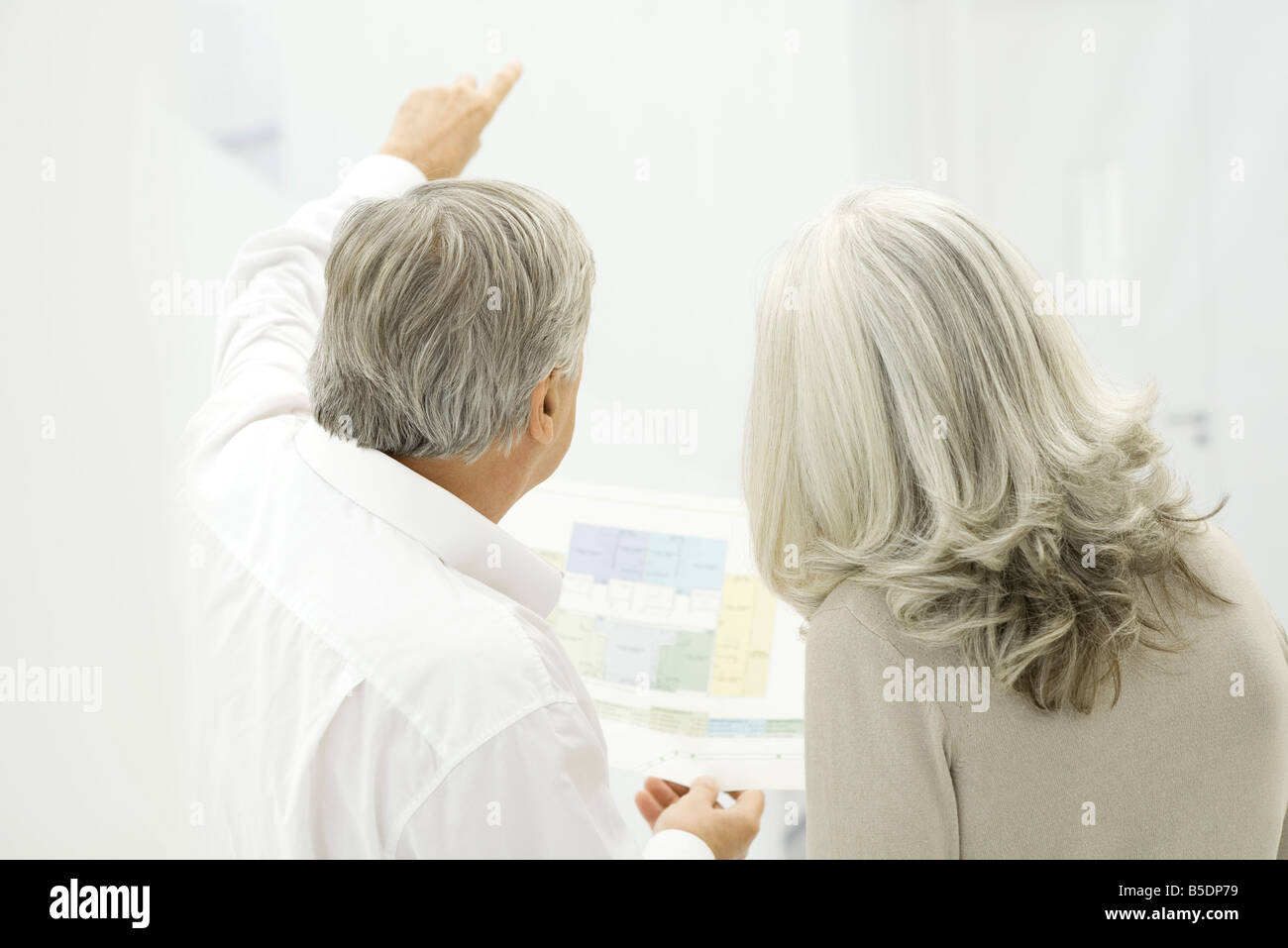Senior couple looking at floor plans, rear view - Stock Image