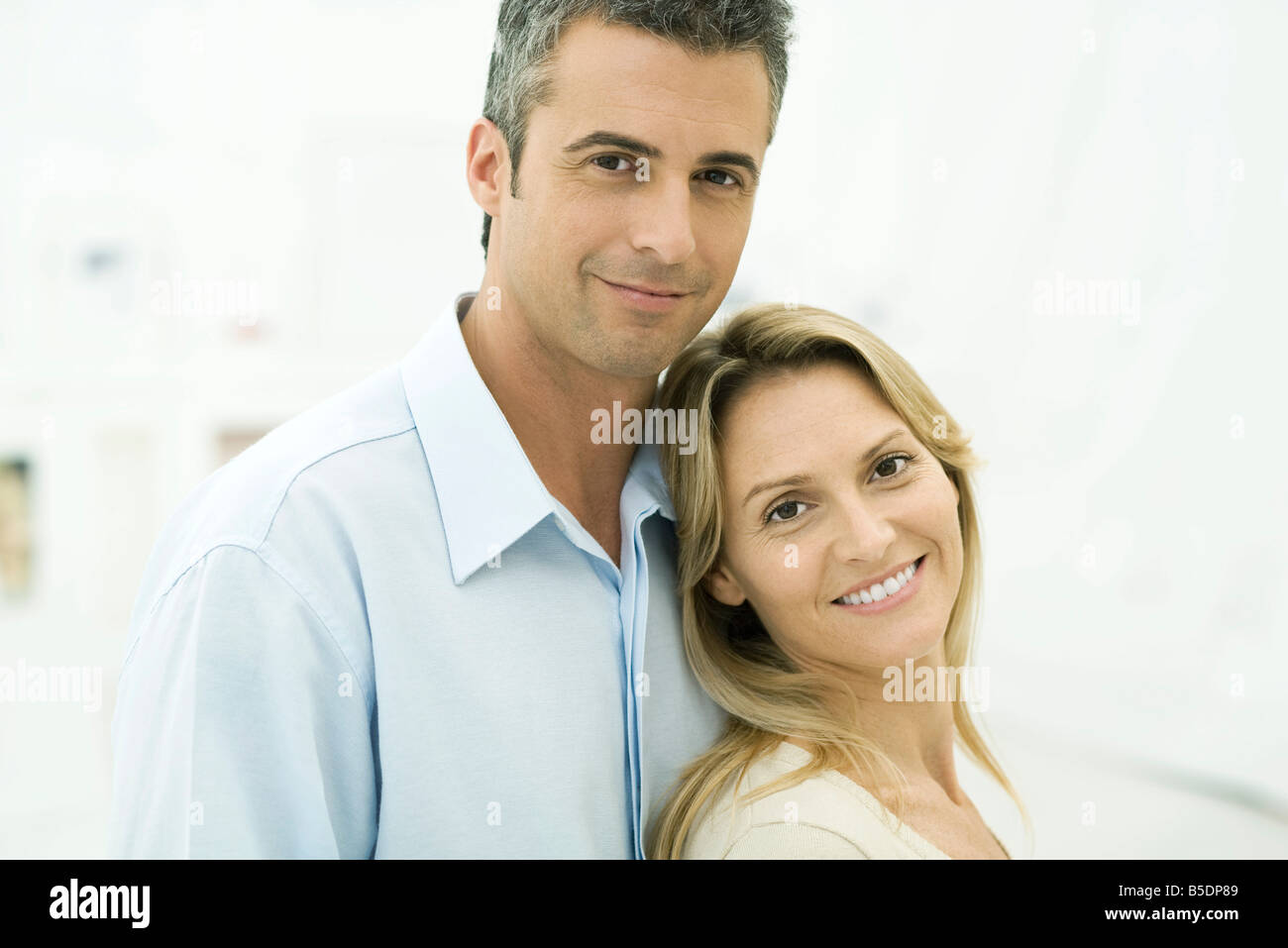 Couple smiling at camera, woman leaning against man, portrait - Stock Image