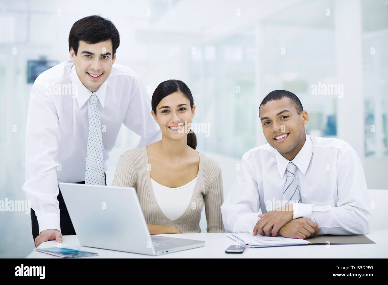 Professionals gathered around laptop computer, smiling at camera - Stock Image