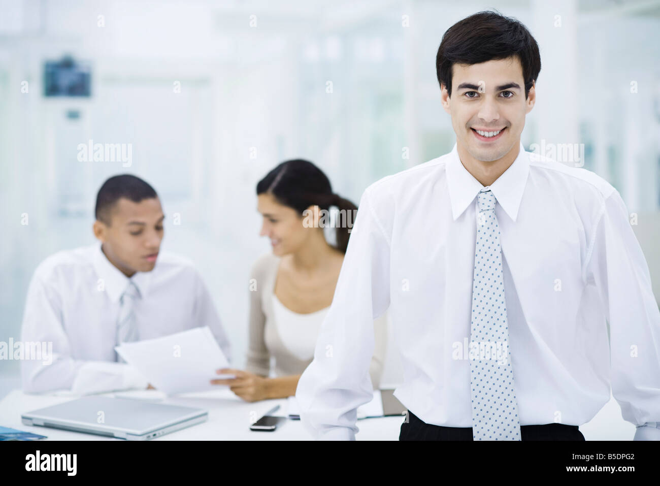 Businessman smiling at camera, colleagues working in background - Stock Image