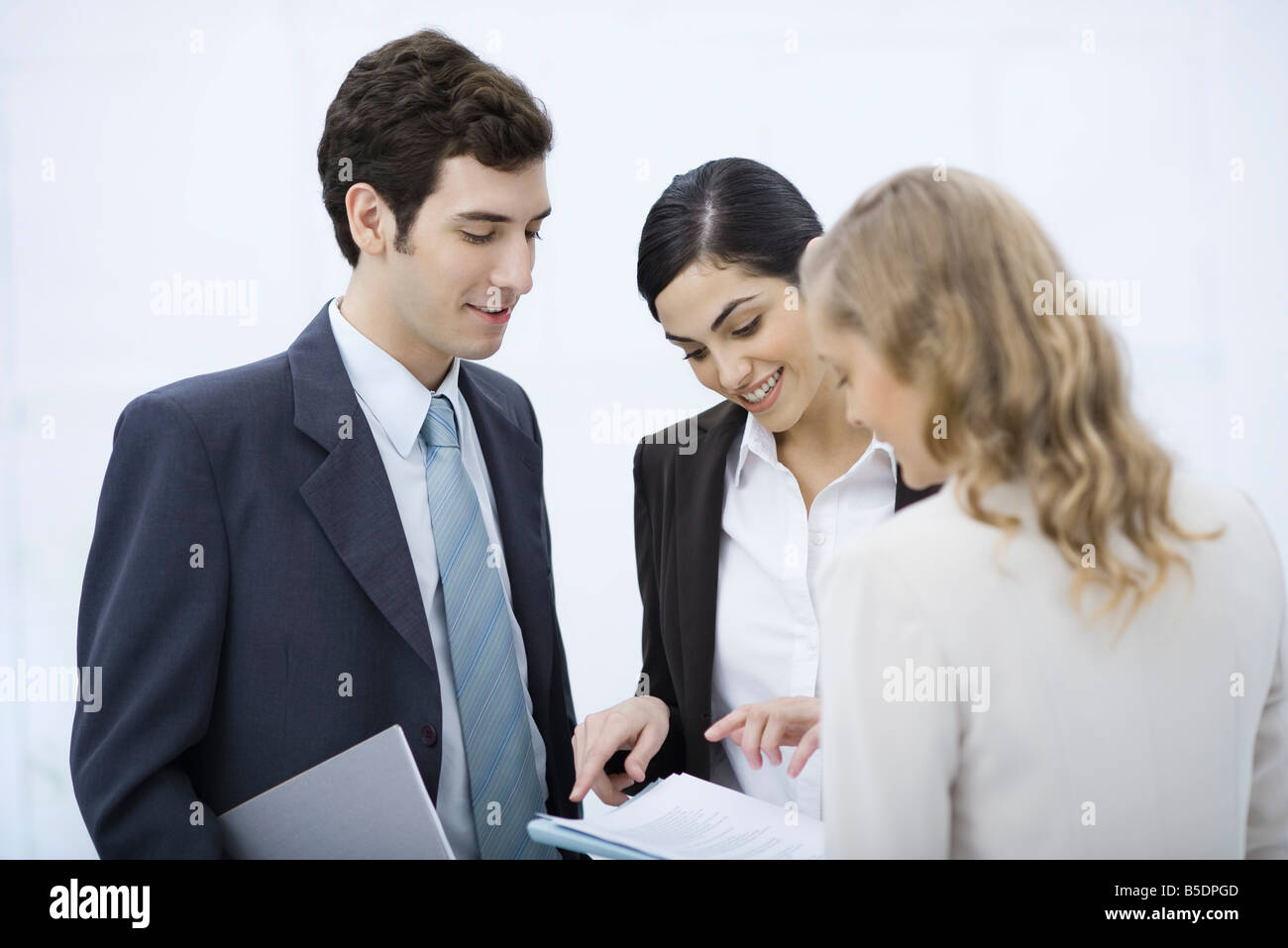 Business associates looking at document together Stock Photo