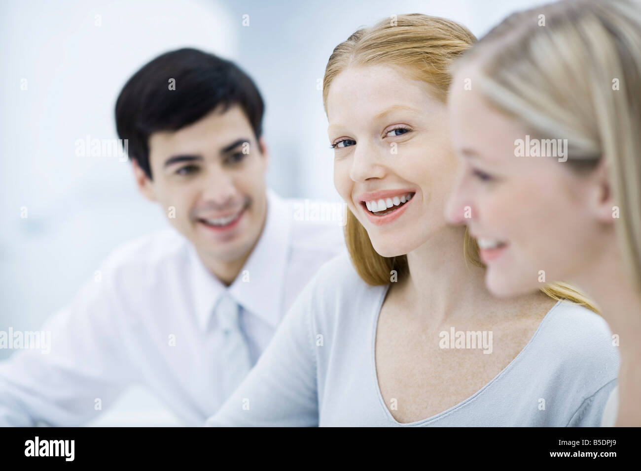 Young professional woman between two colleagues, smiling at camera - Stock Image