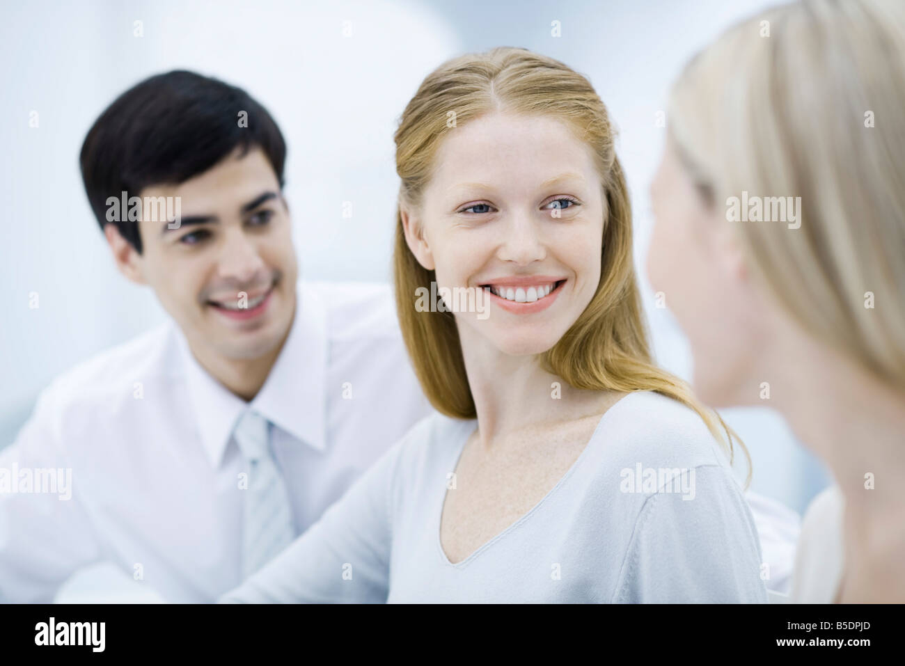 Young professional woman smiling at colleague, close-up - Stock Image