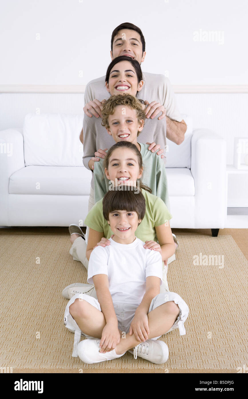 Family lined up shortest to tallest, smiling at camera - Stock Image
