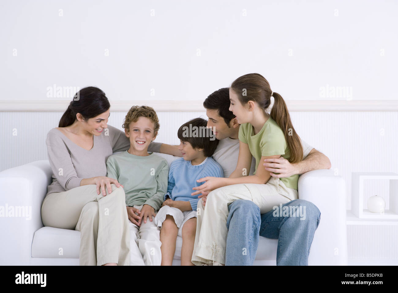 Family with three children sitting together on sofa, one boy smiling at camera Stock Photo