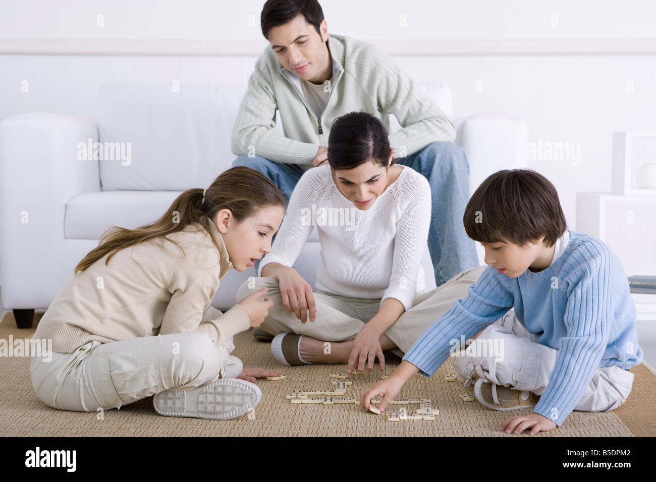 Family spending time together, mother and children playing dominoes, father watching Stock Photo