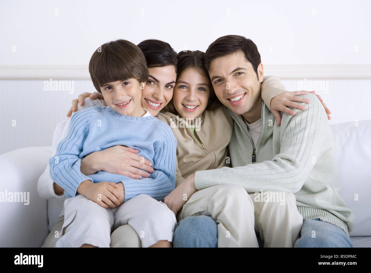 Parents and two children sitting together on sofa, portrait - Stock Image