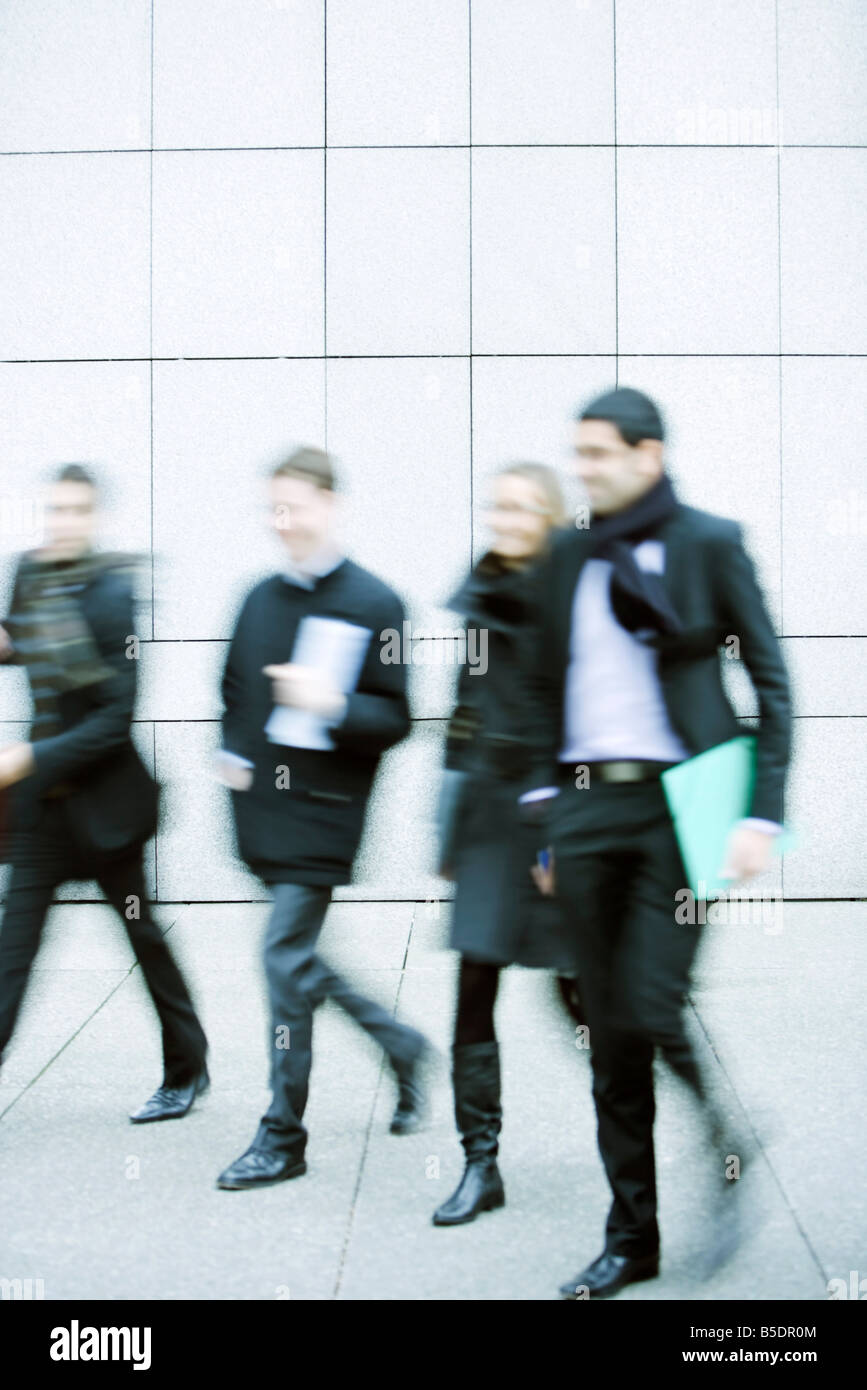 Business associates walking together down sidewalk Stock Photo